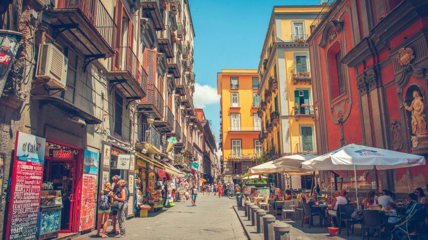 Naples, Italy - July 28, 2015: Narrow street in the center of Naples, with its traditional architecture, cafes and shops.