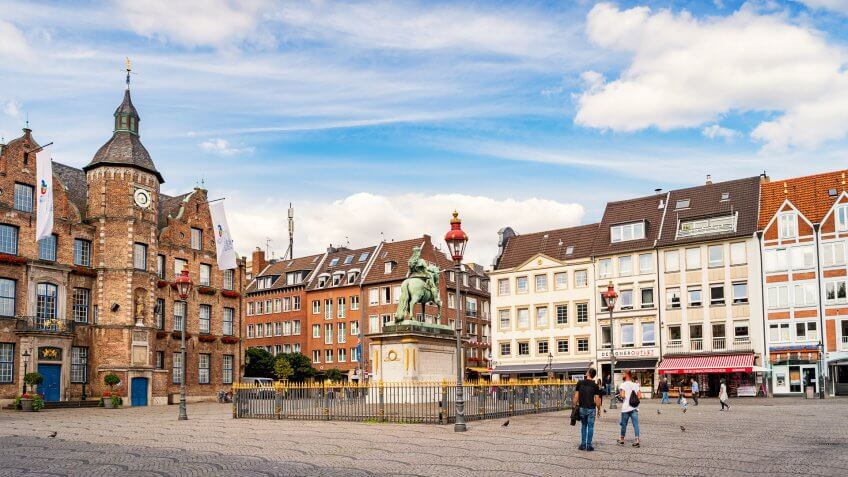 People look at the statue of Jan Wellem located in front of the Old Town Hall on Marktplatz in Old Town Dusseldorf,  North Rhine-Westphalia, Germany.