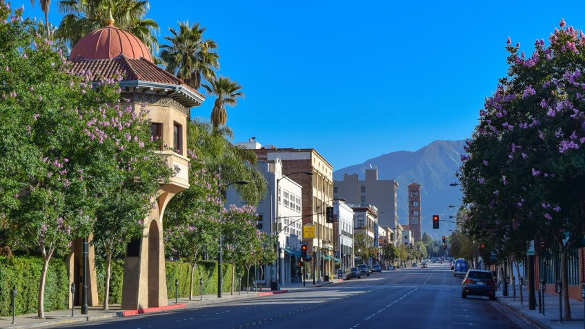 An empty street in downtown Pasadena, California with palm trees and retail stores.