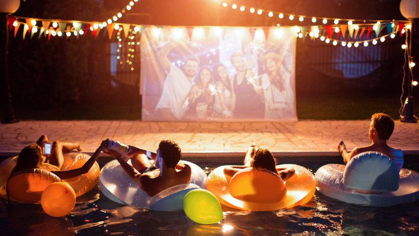 Young friends having pool movie night party.