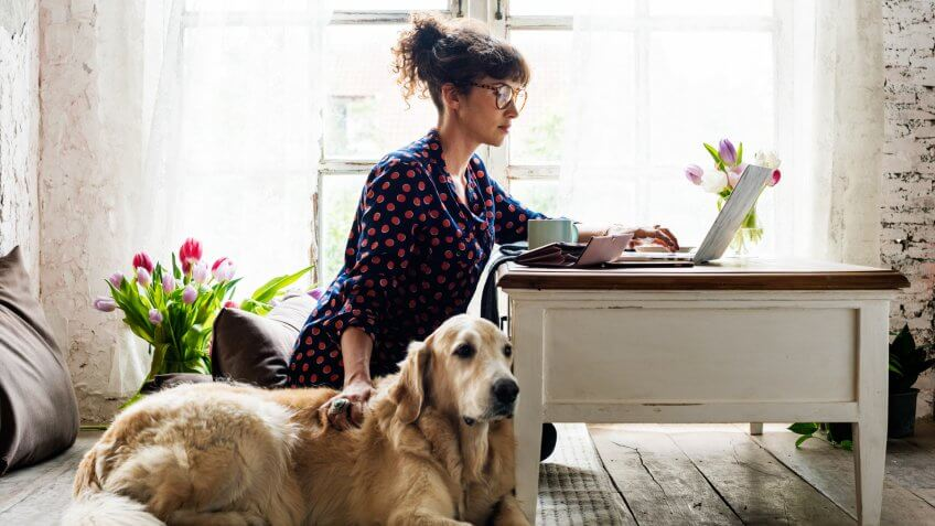 Woman petting dog while working from home