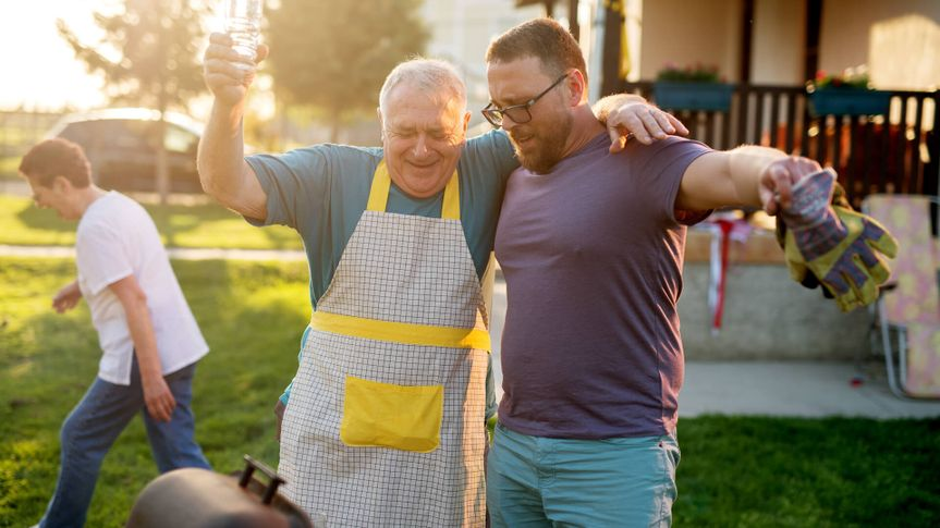 baby boomer father and millennial son barbecuing in backyard