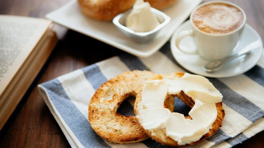 Montreal style bagels on a plate with cream cheese and coffee.