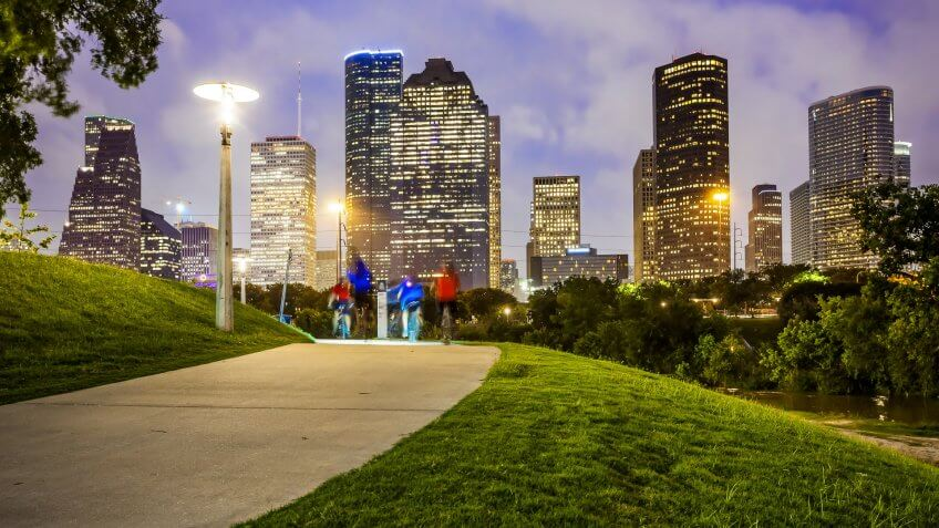 Houston city skyline as night falls and people enjoying Eleanor Tinsley Park.