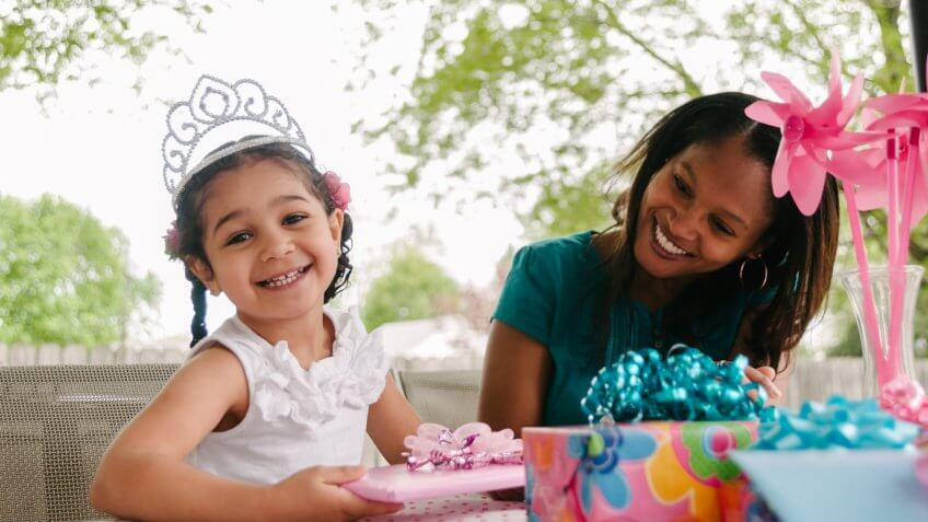 Girl princess tiara opening her gifts with her mother at her birthday party.