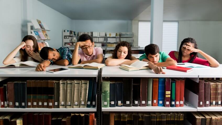 A multi-ethnic group of students leaning on a bookshelf and looking tired and sleepy in a horizontal waist up shot indoors.