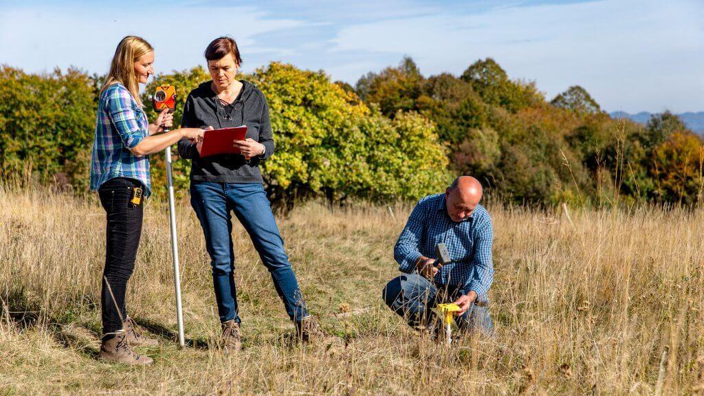 Surveyors Finishing Measurements and Hammering Boundary Marker.