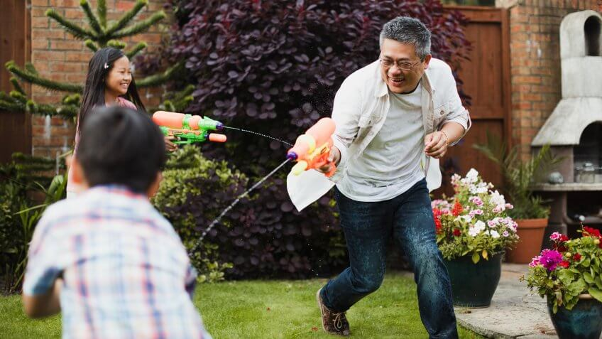 Family are having a water fight together with water pistols in the garden.
