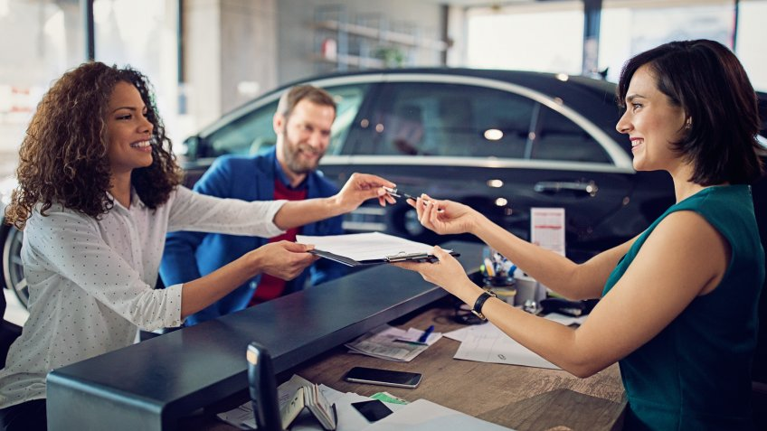 couple signing contract to lease new car