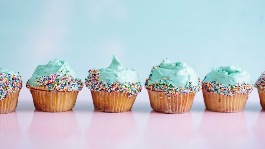 mini cupcakes with light teal frosting and sprinkles in a row