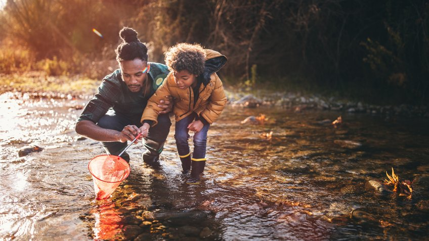 Young dad teaching son how to fish with fishing net in mountain stream at sunset.