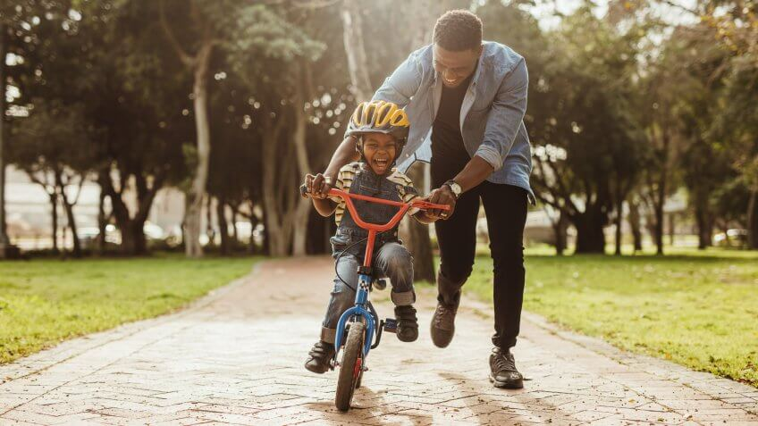 Boy learning to ride a bicycle with his father in park.