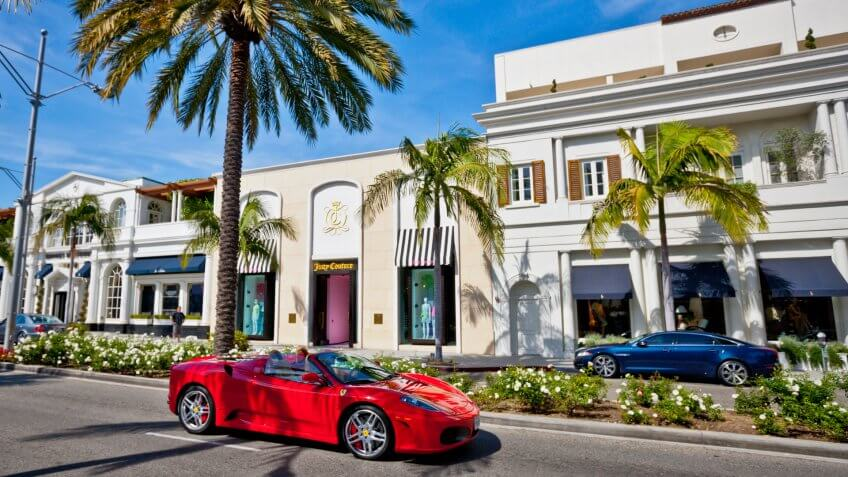 Beverly Hills, USA - May 3, 2013: Rodeo Drive, Beverly Hills, Juicy Couture store on the other side of Rodeo Drive, red Ferrari moving on the street.