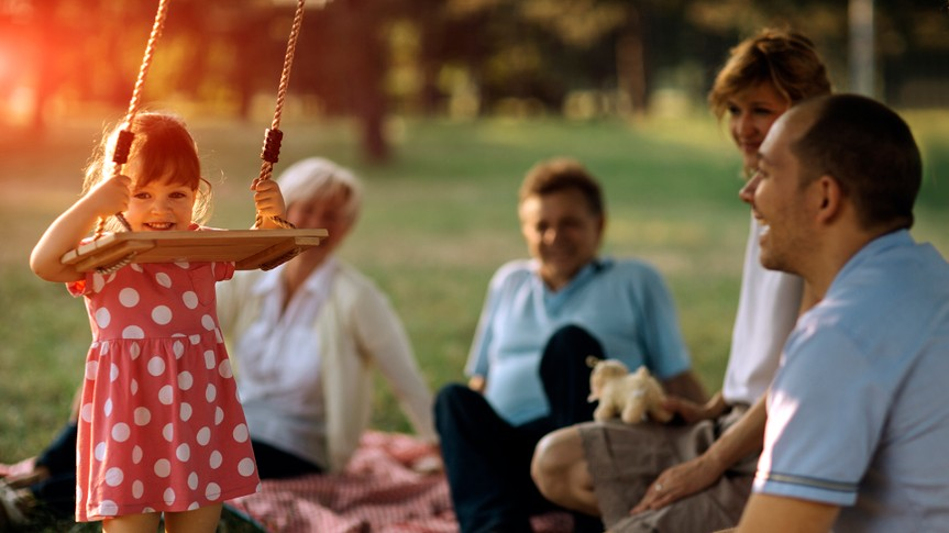 Three generation Family with one child having fun in a park at picnic.