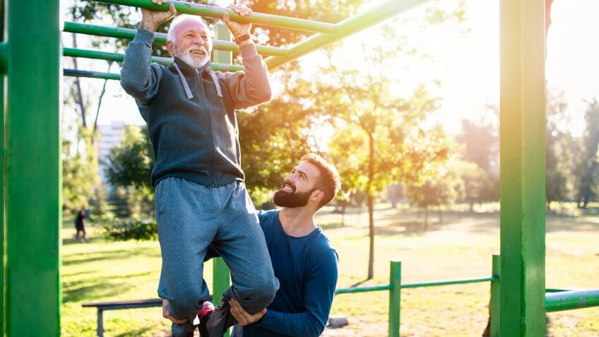 Happy good looking father and son exercising together in park.