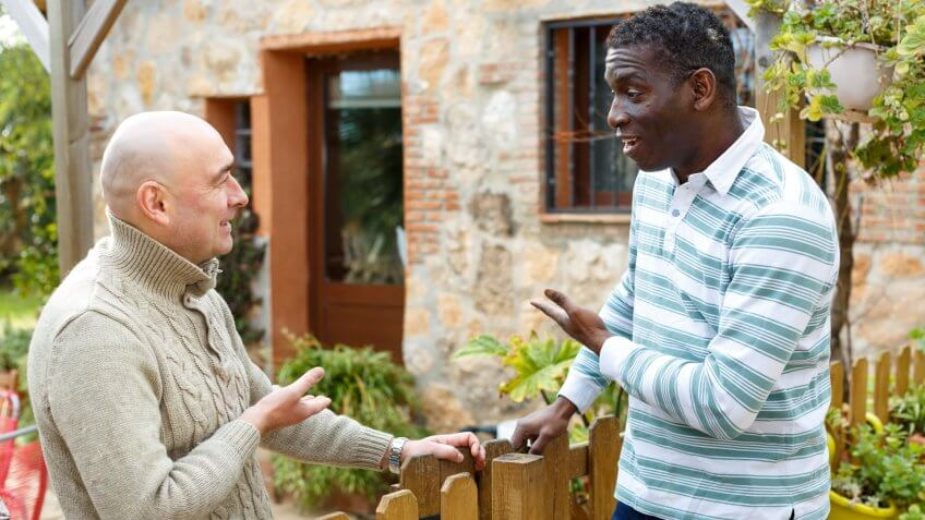 Two male farmers friendly talking outside next to wooden fence on background with brick house.