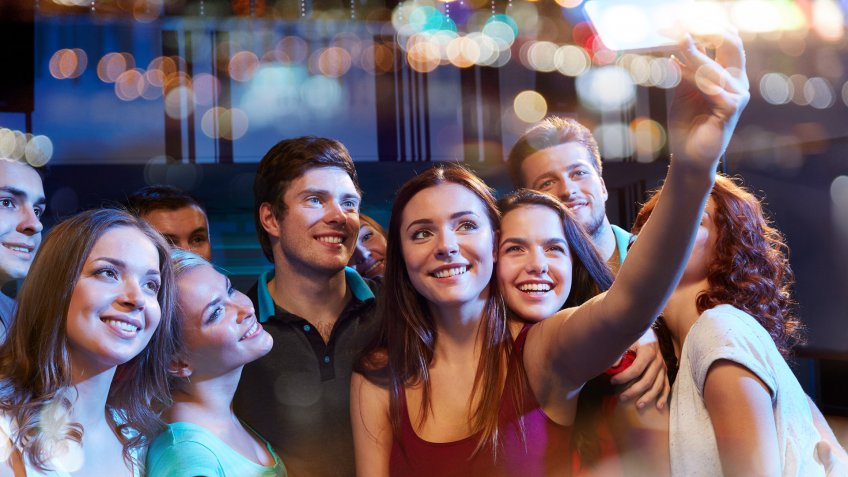 girl taking selfie at party while she is sick from work