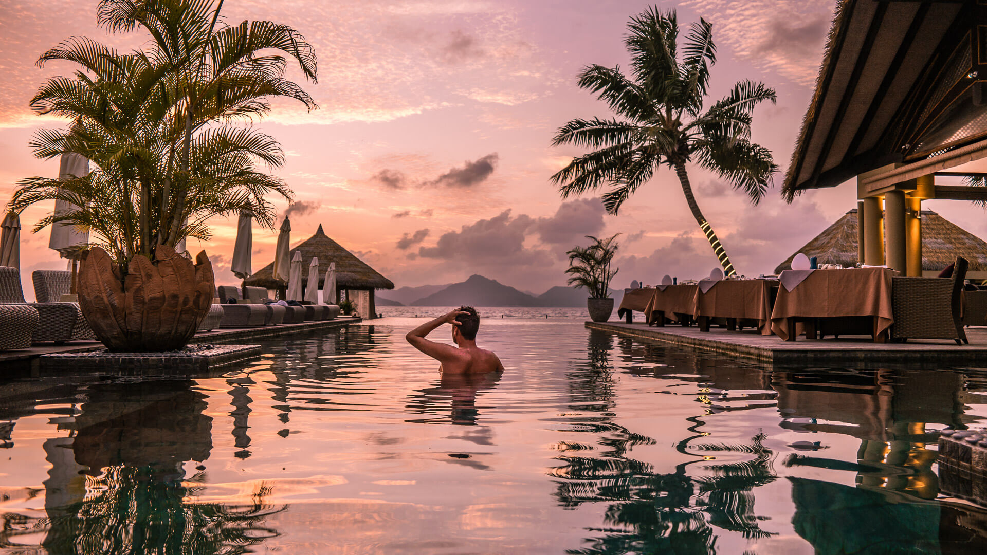 guy swimming in all-inclusive resort vacation