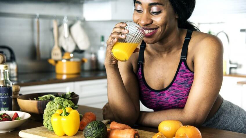 Black woman is drinking orange juice.