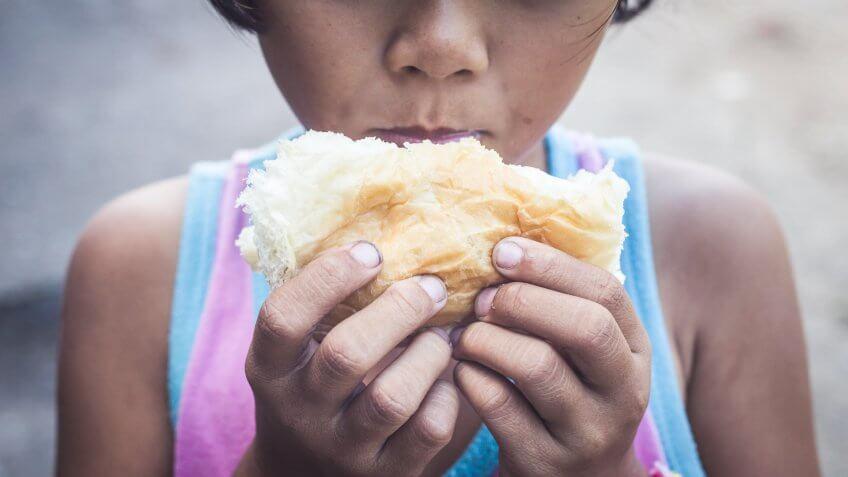 homeless kid eating bread