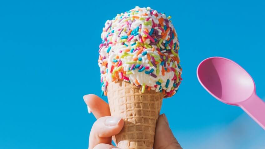 ice cream cone with sprinkles and a pink spoon