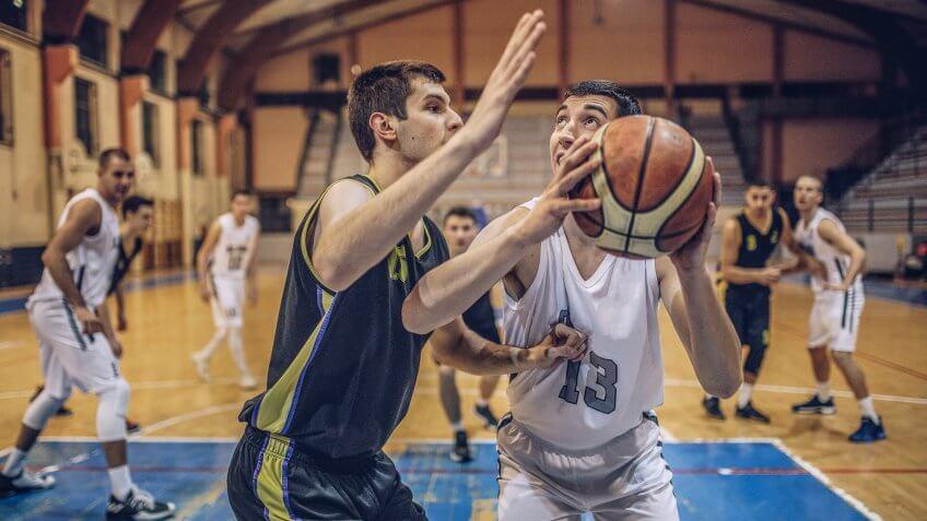 Group of male basketball players playing basketball.