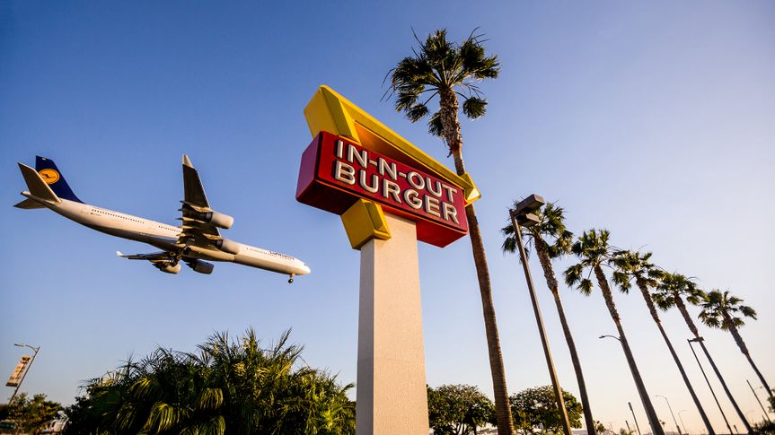 Los Angeles, USA - May 13, 2013: Airplane flying over In-n-Out Burger, LAX, few cars are leaving In-n-out parking lot.