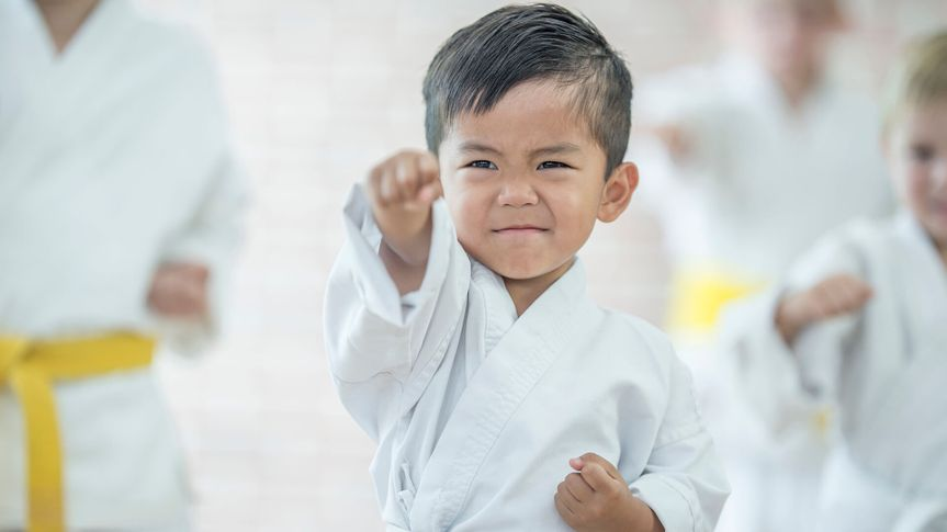 A multi-ethnic group of elementary age children are taking a karate class together at a health club.
