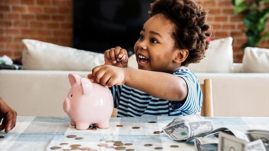 Black boy collecting money to piggy bank.