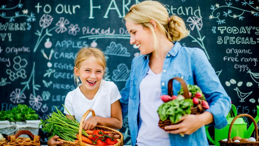 A mother and daughter are at a farmer's market together.