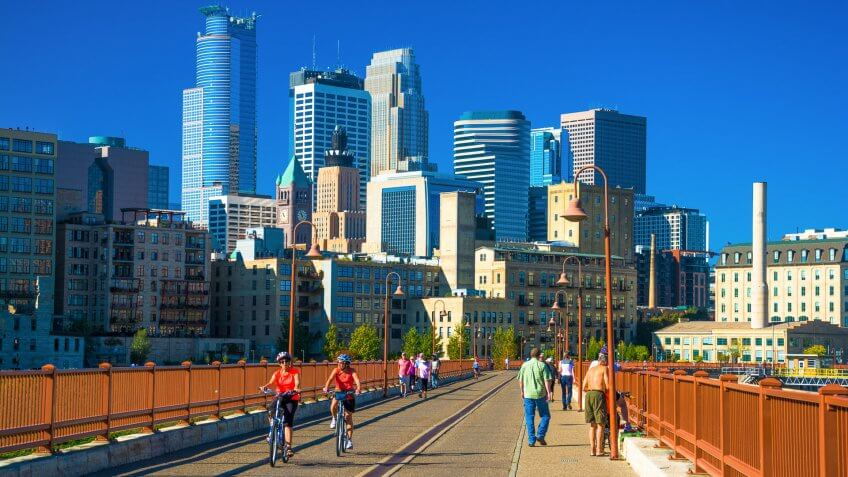 Active people walking and biking on the Stone Arch Bridge during a nice sunny day with the Downtown Minneapolis skyline in the background.