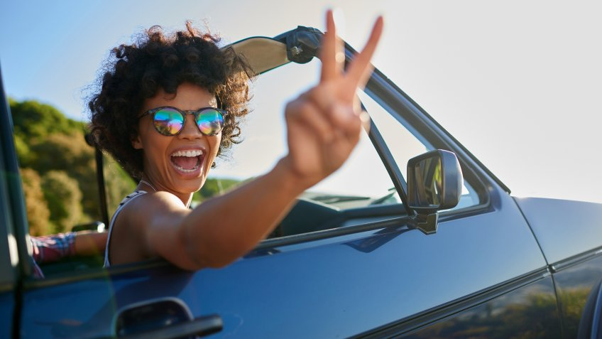 Shoot of young woman leaning out the window of car.