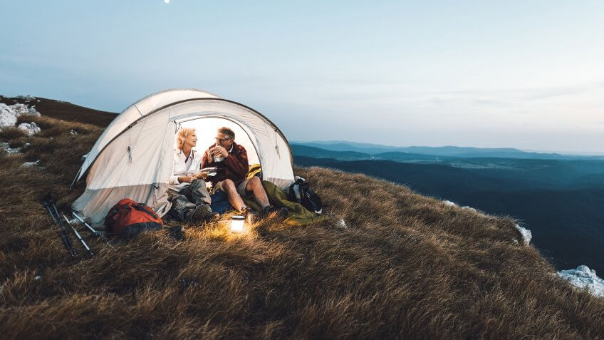 Senior couple camping in the mountains and eating a snack.