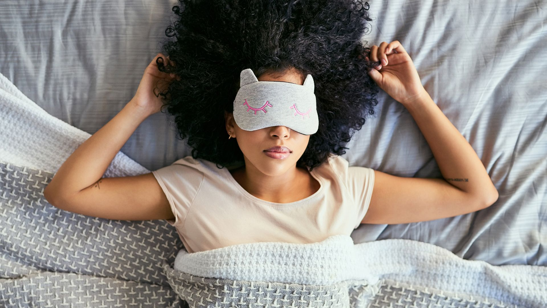 Shot of a young woman sleeping with a mask on in bed.