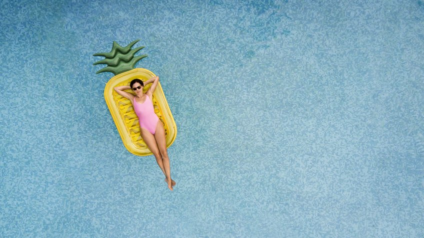 Carefree woman on inflatable pineapple.