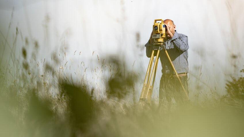 Surveyor Using Theodolite to Measure Land.