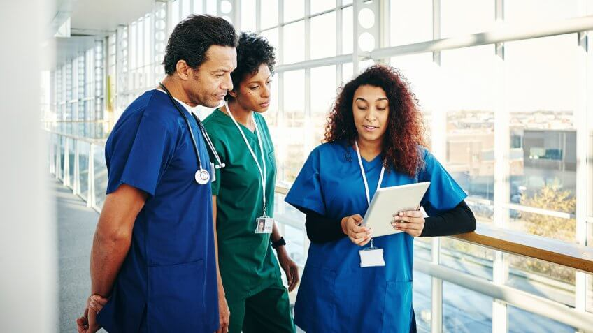 Three doctors in scrubs looking at digital tablet and discussing.