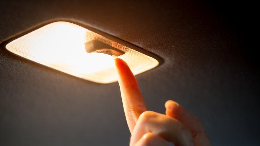 Closeup photo of woman turning light on in car salon.