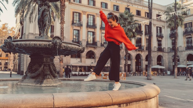 Smiling woman trying to keep balance while walking on one leg at the fountain.