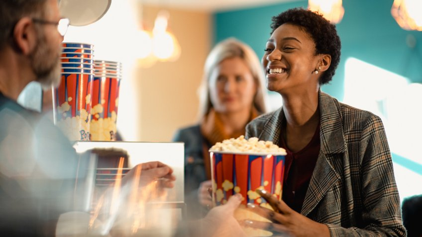 Young female woman buying popcorn at the concession stand while at the movies.