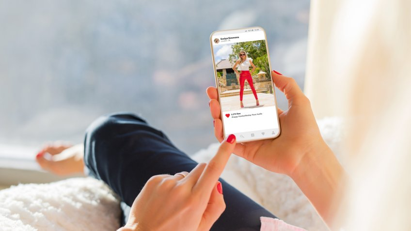 woman looking at slightly risque post on Instagram account