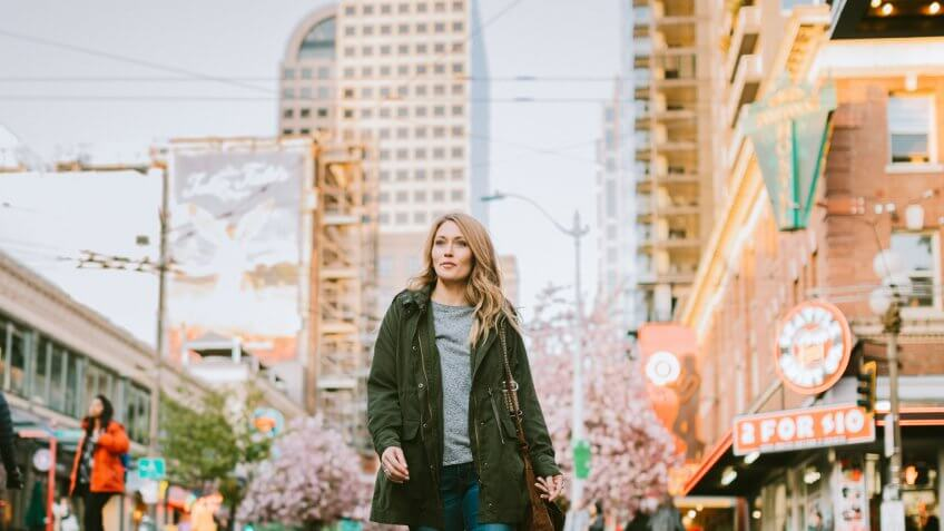 A beautiful and happy woman woman walks around downtown Seattle on a nice day.