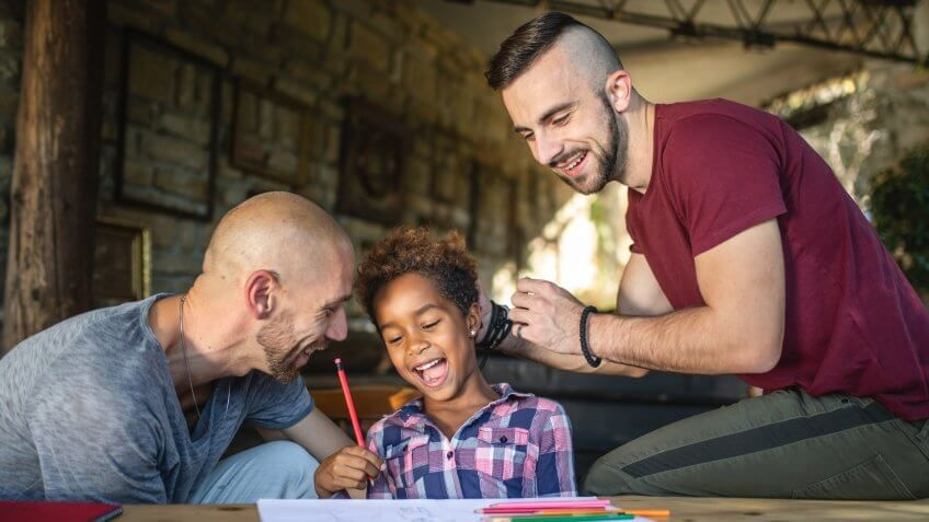 Beautiful and lovely gay homosexual couple enjoying their time spent together as a family with their beautiful adopted mixed race daughter.