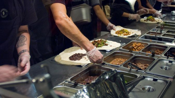 Chipotle workers make burritos for customers