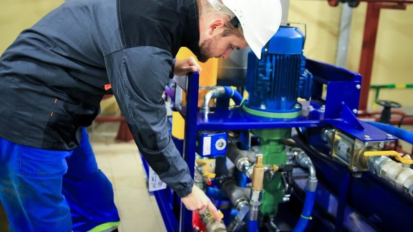 Engineer checking oil pump and pressure gauge in industrial plant.