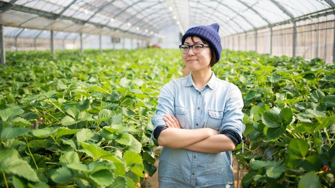 Portrait of a confident small business owner stood inside her farm with her arms crossed.