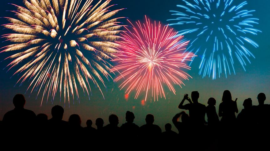 A Fourth of July fireworks display exploding in the sky over a group of people.