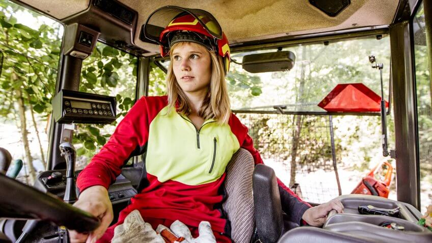 Young Lumberjack Woman Driving a Tractor.