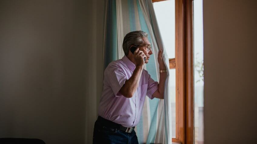 A senior man uses the telephone whilst peeking out of the window.