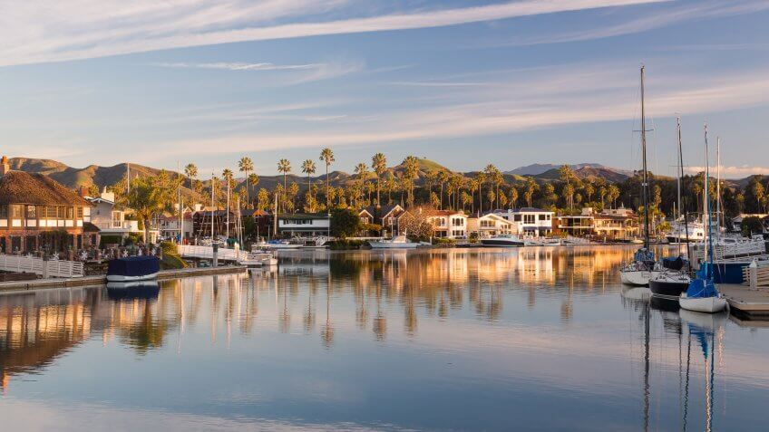 Sunrise at residential development by water in Ventura California with modern homes and yachts boats.